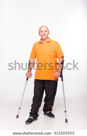 disabled person studio is on crutches isolated on white - stock photo