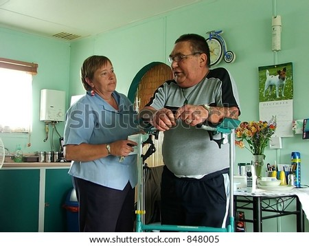 Disabled person with caregiver - stock photo