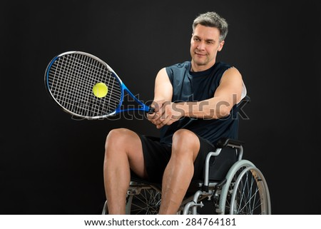 Disabled Player On Wheelchair Playing Tennis On Black Background - stock photo