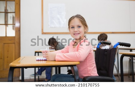 Disabled pupil smiling at camera in classroom at the elementary school - stock photo