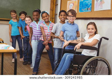Disabled pupil smiling at camera with classmates at the elementary school - stock photo