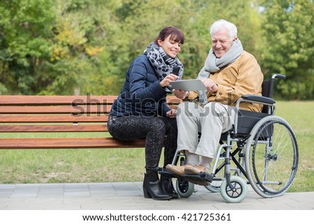 Disabled retiree in park with young carer - stock photo