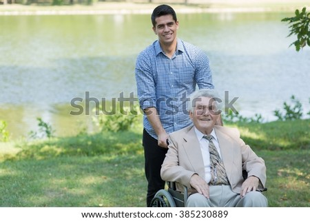 Disabled senior man and grandson spending time outdoors - stock photo
