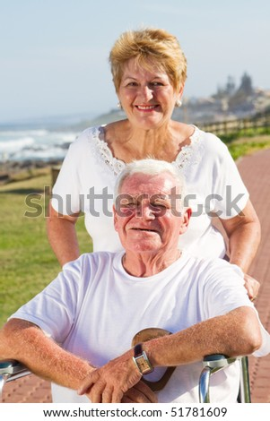 Disabled senior man being pushed by his loving wife at beach on sunny day - stock photo