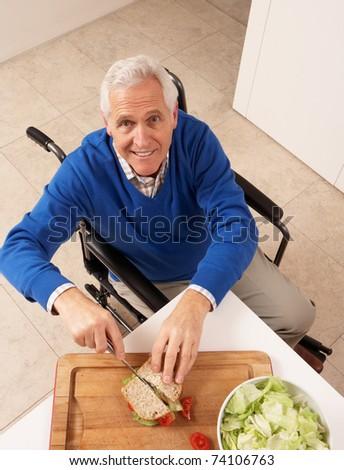 Disabled Senior Man Making Sandwich In Kitchen - stock photo