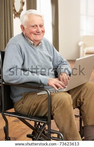 Disabled Senior Man Sitting In Wheelchair Using Laptop - stock photo