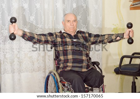 Disabled senior man with an amputated leg sitting in a wheelchair working out with dumbbells to strengthen his upper body and arms - stock photo