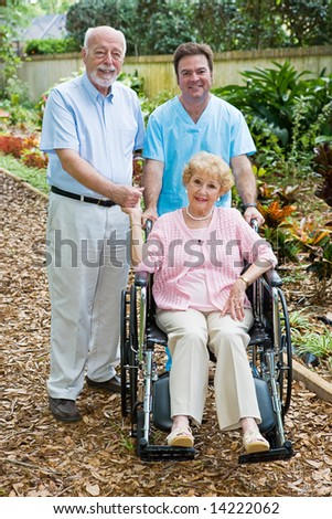 Disabled senior woman and her husband with a male nurse on the grounds of an assisted living facility.  Focus on the woman. - stock photo