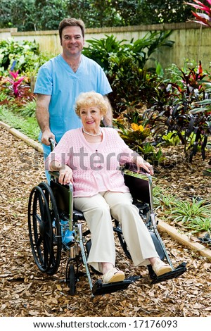 Disabled senior woman in a wheelchair with her male nurse companion. - stock photo