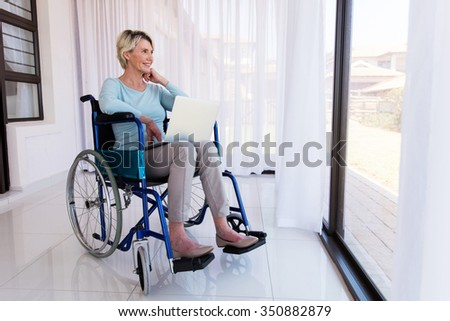 disabled senior woman with laptop relaxing at home - stock photo