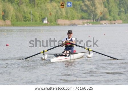 Disabled skiff rower, during a powerful stroke in a rowing regatta - stock photo