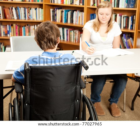 Disabled student in the school library, studying with a classmate.  Focus on the boy in the wheelchair. - stock photo