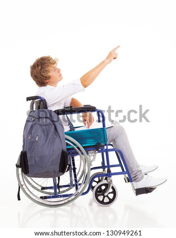 disabled teen boy sitting on wheelchair and pointing on white background - stock photo