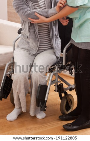 Disabled trying to get up with helper - stock photo