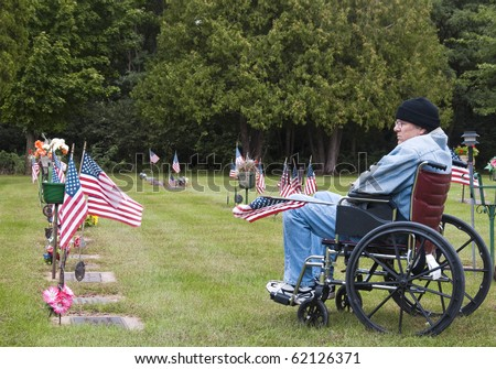 disabled veteran in a wheelchair at the cemetery remembering his fallen brothers - stock photo