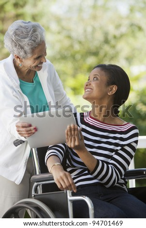 Disabled Woman in a wheelchair sharing a Digital Tablet with her mother - stock photo