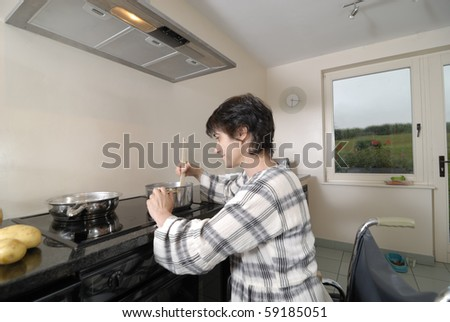 Disabled woman in wheelchair cooking dinner - stock photo