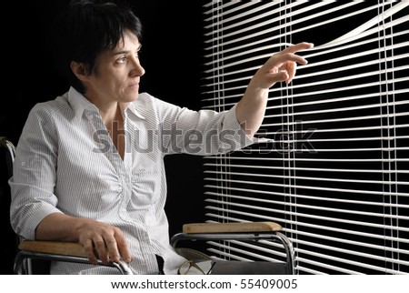 Disabled woman in wheelchair looking trough blinds - stock photo