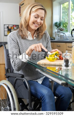 Disabled Woman In Wheelchair Preparing Meal In Kitchen - stock photo