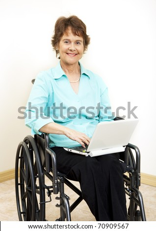 Disabled woman in wheelchair, typing on netbook computer.