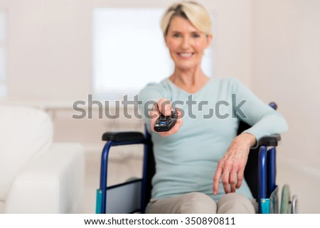 disabled woman in wheelchair watching movies at home - stock photo