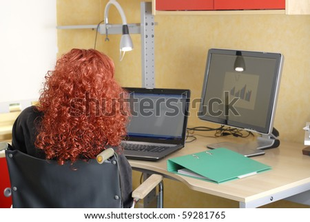 Disabled woman in wheelchair working on the computer at her desk