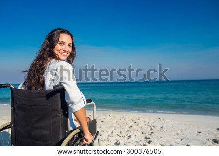 Disabled woman looking at camera on a sunny day - stock photo