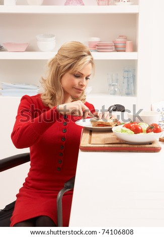 Disabled Woman Making Sandwich In Kitchen - stock photo