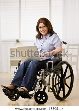 Disabled woman sitting in wheel chair typing on laptop - stock photo