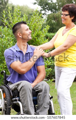 disabled young man in wheelchair and a mature woman touch his hand, care for a wheelchair user