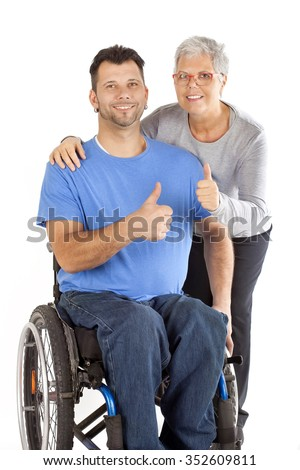 disabled young man in wheelchair and a mature woman with thumbs up, care for a wheelchair user