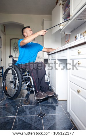Disabled young man in wheelchair for reaching dishes from cupboard - stock photo