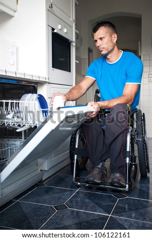 Disabled young man in wheelchair gives the dishwasher on - stock photo