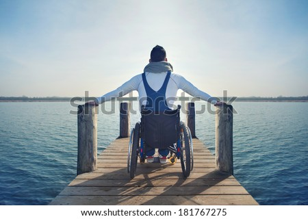 disabled Young man in wheelchair on a boardwalk on lake enjoying his freedom  - stock photo