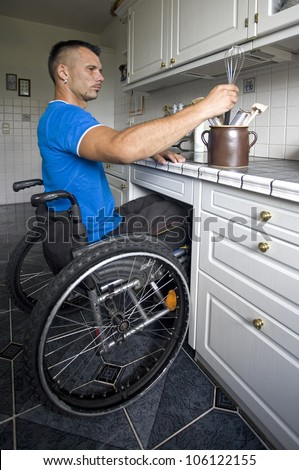 Disabled young man in wheelchair preparing dinner in the kitchen - stock photo
