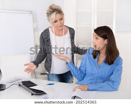 Disagreement, bullying and trouble under two business woman at work. - stock photo