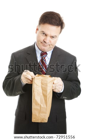 Disappointed businessman having to bring his lunch in a bag to save money.  Isolated. - stock photo