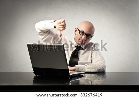 Disappointed businessman sitting in front of his pc - stock photo