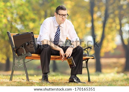 Disappointed businessman sitting on a wooden bench with bottle in his hand, in park - stock photo