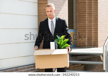 Disappointed Businessman Standing With Cardboard Box Outside Office - stock photo