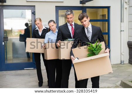 Disappointed Businesspeople Standing In A Row With Cardboard Boxes Outside The Office - stock photo