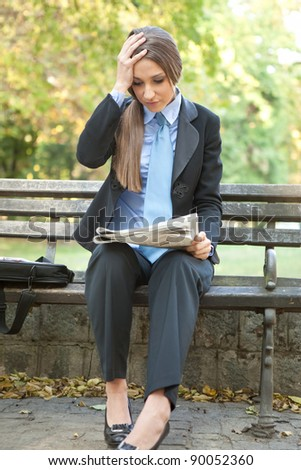 disappointed businesswoman holding her head and reading bad  news - stock photo