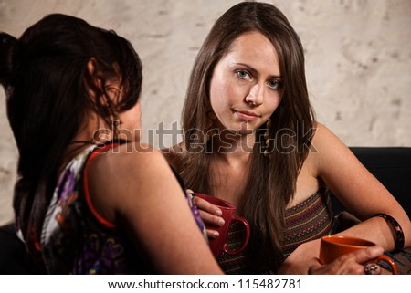 Disappointed Caucasian brunette female sitting indoors with another lady - stock photo