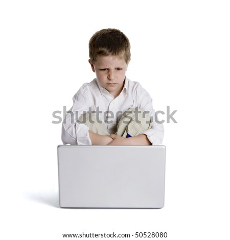 Disappointed child sitting in front of laptop computer, studio shot isolated on white background - stock photo