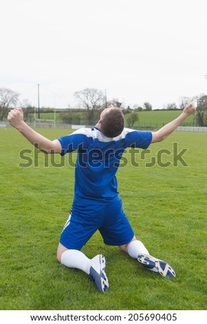 Disappointed football player in blue sitting on pitch after losing on a clear day - stock photo