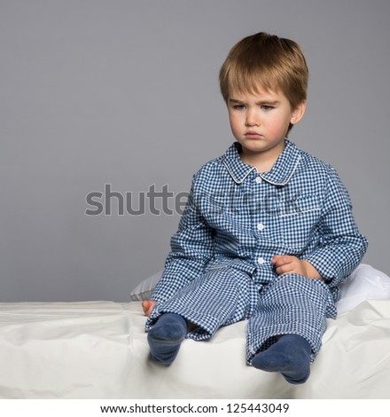 Disappointed little boy in blue pyjamas on bed - stock photo
