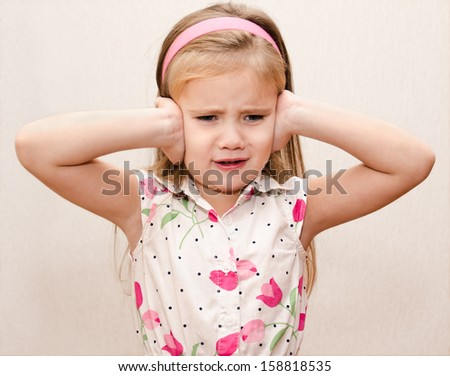 Disappointed little girl covering her ears - stock photo