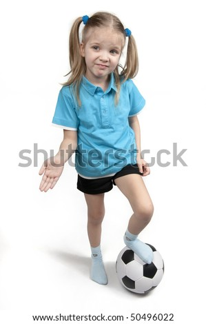 disappointed little girl holding her foot on a football. - stock photo