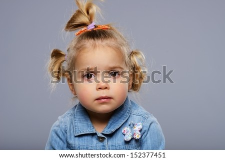 Disappointed little girl isolated on grey background  - stock photo