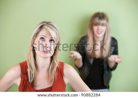Disappointed mom with frustrated daughter in background
